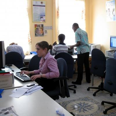 A volunteer teaching computer skills to a student in Ghana